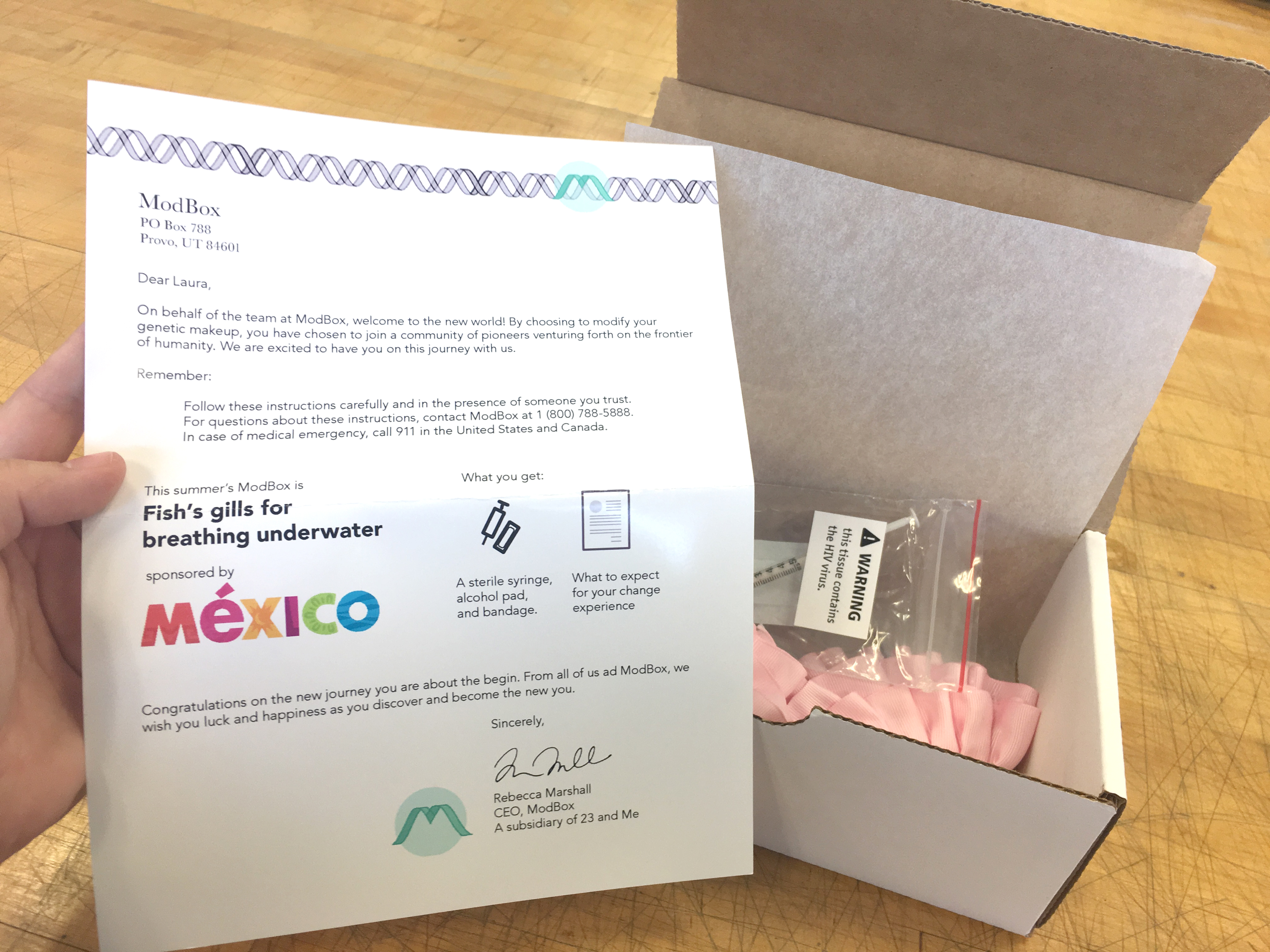 The box is open and includes a letter welcoming the customer to the frontier of humanity. The box includes a syringe and supplies to genetically modify a human with fish gills for breathing underwater. It's sponsored by Mexico tourism.