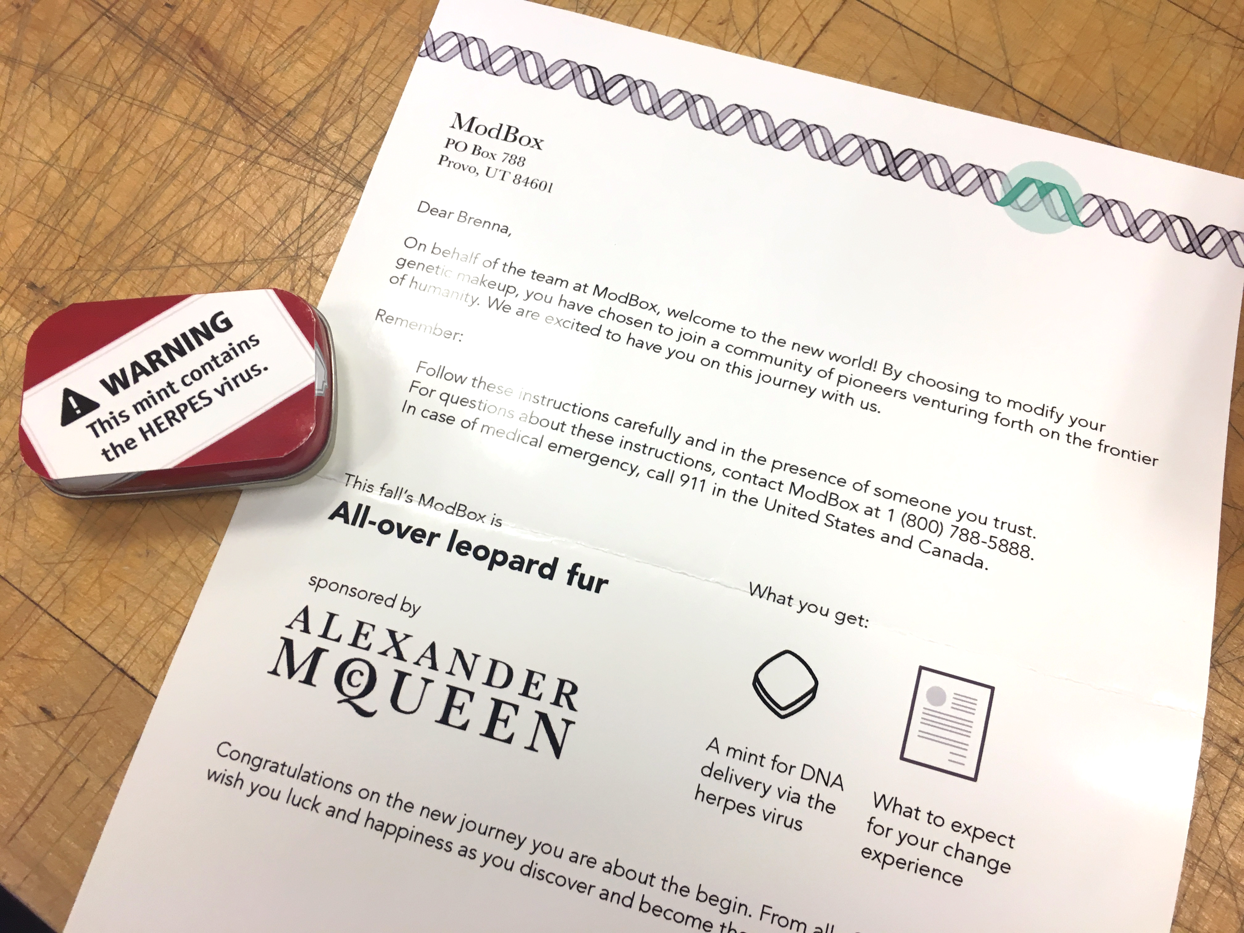 A letter welcomes another customer to the frontier of humanity with supplies to genetically modify a human with all-over leopard fur. It's sponsored by Alexander McQueen. There is a mint tin that contains the herpes virus, how the genetic modifcation is delivered.