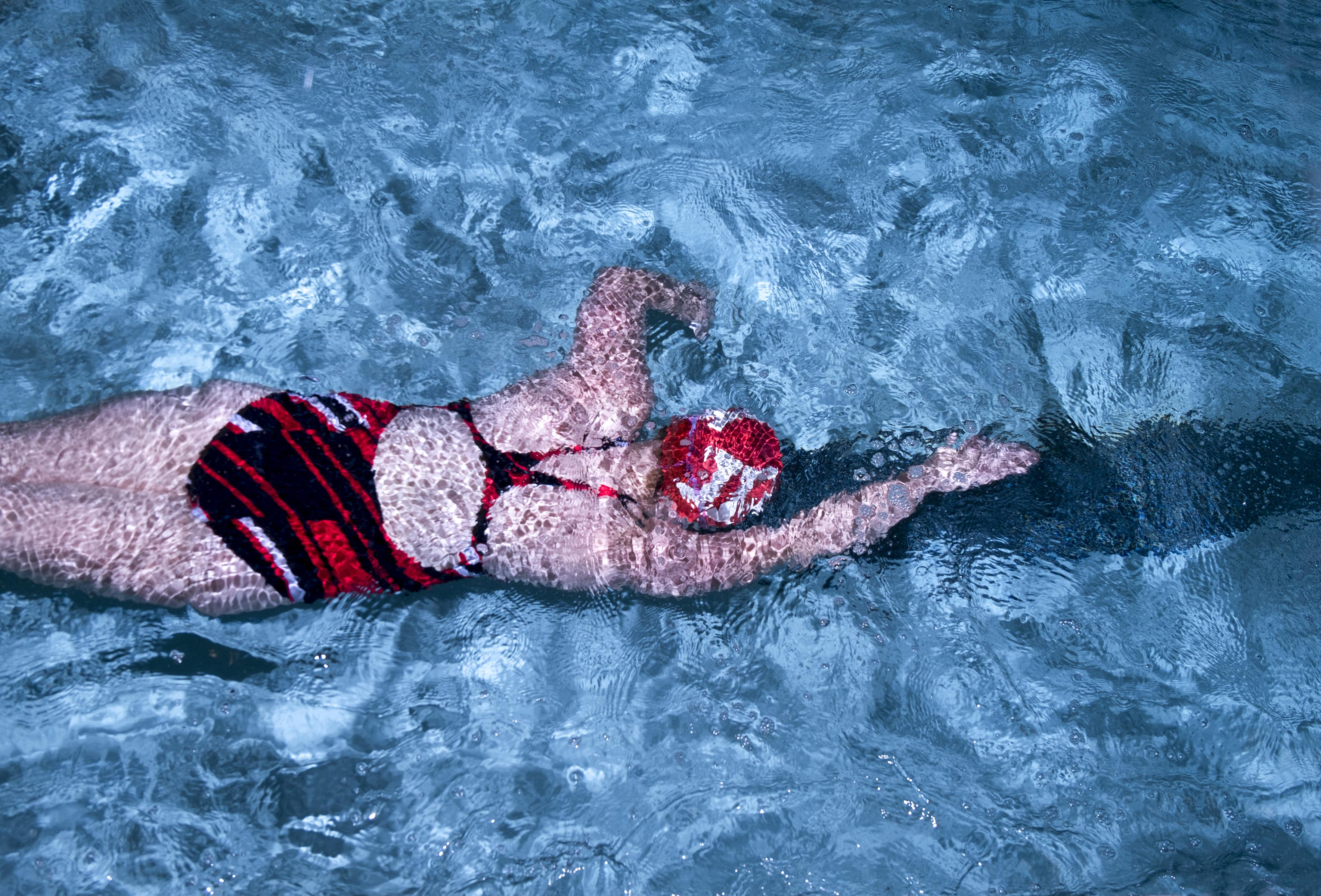 A photograph of a woman in a red swimsuit and a red swimcap, swimming in a pool, shot from above.