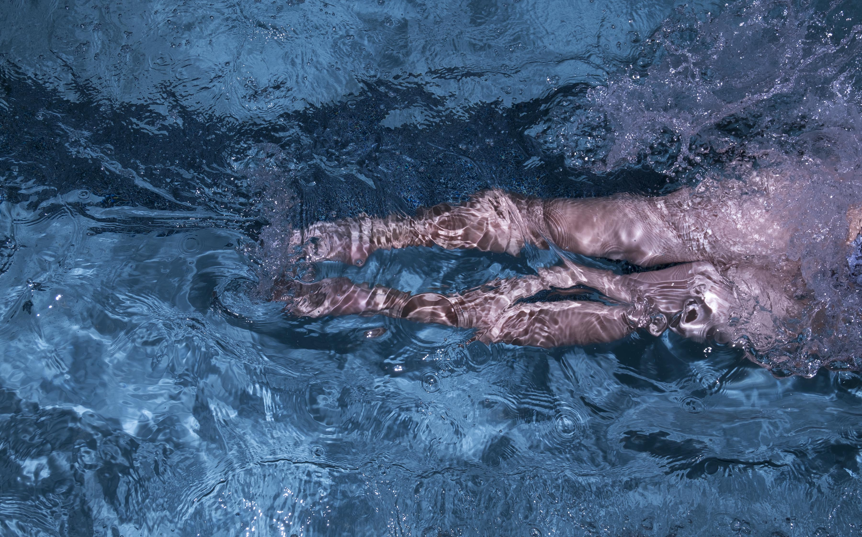 A photograph of a woman's legs disappearing to the right as she swims in a pool lane, splashing lots of water, shot from above.