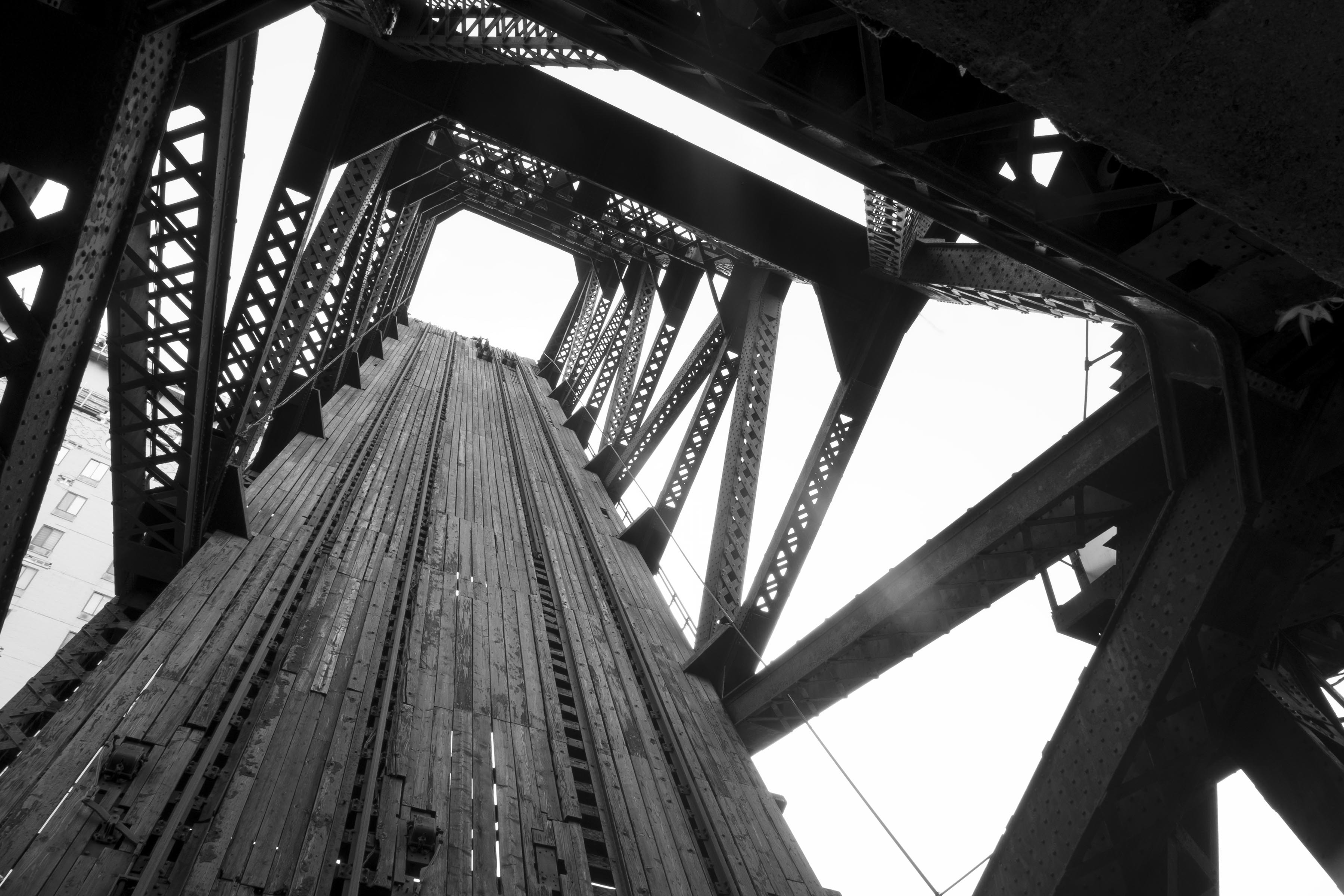 A photograph of a lifted rail bridge, photographed up from inside it.